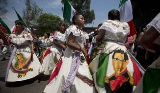 ** FILE ** Women dressed as a revolutionary Zacapoaztla Indian soldiers dance during a re-enactment of the battle of Puebla between the Zacapoaztlas Indians and French army at the Cinco de Mayo celebrations, in Mexico City, Monday May 5, 2014. Cinco de Mayo commemorates the victory of an ill-equipped Mexican army over French troops in Puebla on May 5, 1862.  (AP Photo/Eduardo Verdugo)