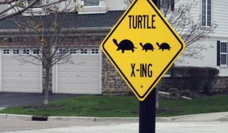 """In this May 1, 2014 photo, a turtle crossing sign is seen posted in a subdivision in Vernon Hill, Ill.  The suburban Chicago community wants fast drivers to hit the brakes to make way for turtles. Vernon Hills Public Works Director David Brown says the village is on a mission because there was """"a significant amount of carnage last year"""" when dozens of turtles died while inching across roads. (AP Photo/Daily Herald, Mick Zawislak)  MANDATORY CREDIT, MAGS OUT"""