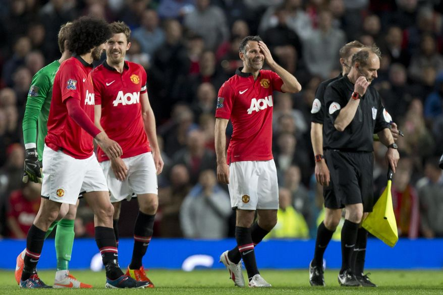 Manchester United's interim manager Ryan Giggs, centre right, smiles after his team's English Premier League soccer match against Hull City,  at Old Trafford Stadium, Manchester, England, Tuesday May 6, 2014. (AP Photo/Jon Super)