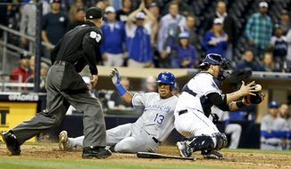 Kansas City Royals' Salvador Perez beats the throw to San Diego Padres catcher Yasmani Grandal while scoring the go ahead run in the 12th inning of a baseball game Monday, May 5, 2014, in San Diego.  (AP Photo/Lenny Ignelzi)