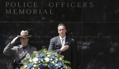 Trooper William Gannon of the New York State Police and Lt. Gov. Robert Duffy stand behind a wreath after placing it at the State of New York Police Officers Memorial on Tuesday, May 6, 2014, in Albany, N.Y. The names of 20 police officers who died in the the line of duty were added to the memorial, including 13 who died from ground zero-related illnesses after the 9/11 attacks. (AP Photo/Mike Groll)