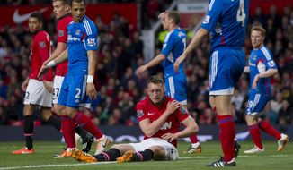 Manchester United's Phil Jones, bottom centre, sits injured on the pitch prior to being substituted, during his team's English Premier League soccer match against Hull City,  at Old Trafford Stadium, Manchester, England, Tuesday May 6, 2014. (AP Photo/Jon Super)