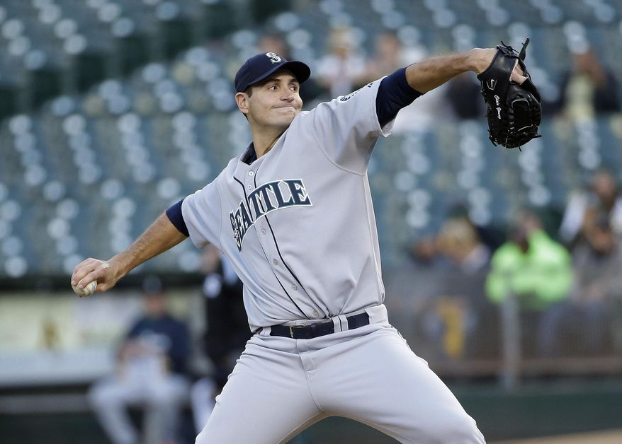 Seattle Mariners starting pitcher Chris Young throws to the Oakland Athletics during the first inning of a baseball game on Monday, May 5, 2014, in Oakland, Calif. (AP Photo/Marcio Jose Sanchez)
