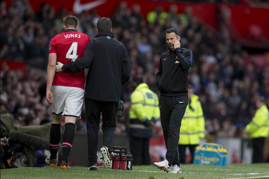 As interim manager Ryan Giggs, right, looks on Manchester United's Phil Jones, left, is helped down the touchline after being substituted injured during his team's English Premier League soccer match against Hull at Old Trafford Stadium, Manchester, England, Tuesday May 6, 2014. (AP Photo / Jon Super)