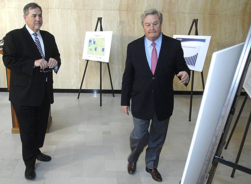 U.S. Census Bureau Director John Thompson, left, looks on as North Dakota Gov. Jack Dalrymple shows him one of the charts illustrating large growth in North Dakota counties during a news conference Tuesday, May 6, 2014, at the state Capitol in Bismarck, N.D. Thompson says the agency is up to the challenge of counting North Dakota's exploding population. (AP Photo/The Bismarck Tribune, Mike McCleary)