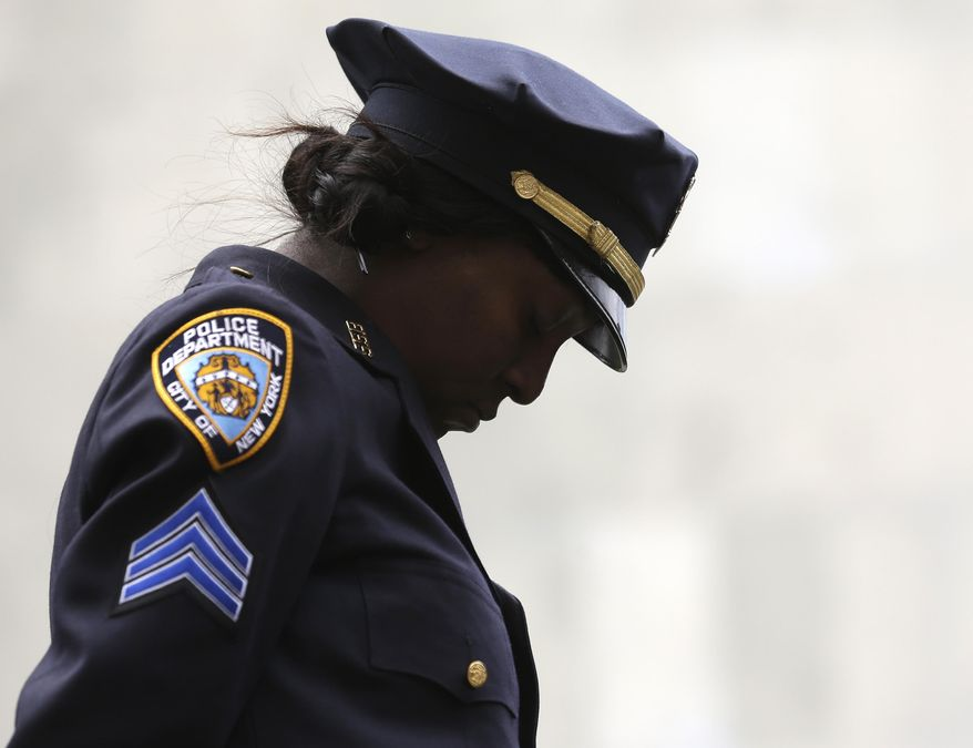 Sgt. Shannon Graham of the New York Police Department bows her head during the benediction during a ceremony at the State of New York Police Officers Memorial on Tuesday, May 6, 2014, in Albany, N.Y. The names of 20 police officers who died in the the line of duty were added to the memorial, including 13 who died from ground zero-related illnesses after the 9/11 attacks. (AP Photo/Mike Groll)