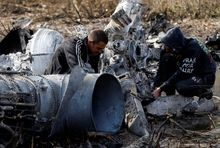 Local citizens collect parts of a downed Ukrainian military helicopter near Raigorodok, outside Slovyansk.