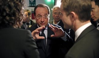 France's President Francois Hollande, center, gestures as he talks to the media after an interview with BFM television journalist in Paris, Tuesday, May 6, 2014. Hollande celebrates Tuesday his second anniversary in charge. (AP Photo/Thibault Camus, Pool)