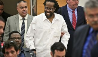 Robert Hill, center, smiles as he is escorted into Brooklyn Supreme Court, Tuesday May 6, 2014 in New York.   Hill and his half brothers Alvena Jennette and Darryl Austin were exonerated in a decades-old conviction investigated by homicide detective Louis Scarcella, whose tactics have come into question.   (AP Photo/Bebeto Matthews)