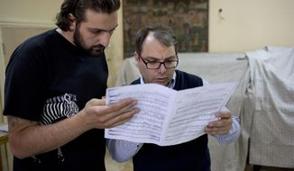 In this Sunday, May 4, 2014 photo, Syrian National Symphony Orchestra conductor Missak Baghboudarian, right, talks to a singer during a practice at art school which adjoins the Damascus Opera House  in Damascus Syria. Two students were killed and five others were wounded when a mortar landed outside the Opera building in April 2014. (AP Photo/Dusan Vranic)