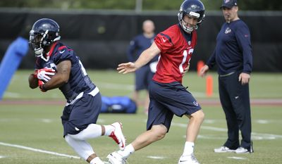 New Houston Texans coach Bill O'Brien, right, watches quarterback T.J. Yates (13) hand off the ball to running back Dennis Johnson, left, during a voluntary veteran NFL football minicamp Tuesday, May 6, 2014, in Houston. He takes over a team that was expected to contend for a Super Bowl but instead fell to a league-worst 2-14 last season. (AP Photo/Pat Sullivan)