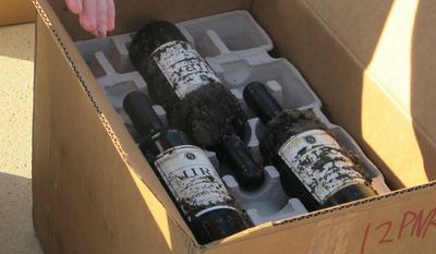Wine that had just been recovered after being aged in Charleston Harbor for six months is loaded into a box on a dock in Charleston, S.C., on Tuesday, May 6, 2014, The Mira Winery is conducting an ongoing experiment to gauge the effect of ocean aging on wine. Other cases of wine had been aged in the harbor last year for three months. (AP Photo/Bruce Smith)