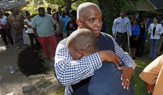 Dwayne Pickett comforts his son Julian, foreground, in Byram, Miss., Tuesday, May 6, 2014 following a news conference calling attention to the death of his best friend and fellow coach Justin Griffin, 25, an AAU youth basketball coach, who died Monday after a fight  over calls with a referee who was an off duty Hinds County Sheriff's Department deputy.  Griffin died from blunt-force trauma to the head due to injuries suffered in the fight, Hinds County Coroner Sharon Grisham-Stewart said.  (AP Photo/Rogelio V. Solis)