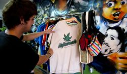 """A shopper looks at a T-shirt decorated with a marijuana leaf and the word """" Mujicannabis,"""" a combination of the president's last name """"Mujica"""" and cannabis, at a head shop in downtown Montevideo, Uruguay, Tuesday, May 6, 2014. Uruguay's President Jose Mujica is set to sign a law creating the country's legal marijuana market,making Uruguay the first country in the world to create a nationwide market regulating the cultivation, sale and use of legal marijuana. (AP Photo/Matilde Campodonico)"""