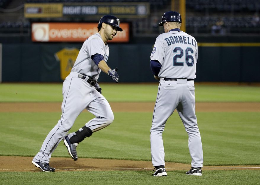 Seattle Mariners' Stefen Romero, left, shakes hands with third base coach Rich Donnelly after Romero's solo home run against the Oakland Athletics during the fifth inning of a baseball game on Monday, May 5, 2014, in Oakland, Calif. (AP Photo/Marcio Jose Sanchez)