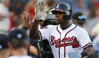 Atlanta Braves' Justin Upton (8) is greeted by his teammates at the dugout after hitting a solo-home run in the fourth inning of a baseball game against the St. Louis Cardinals, Tuesday, May 6, 2014, in Atlanta. (AP Photo/John Bazemore)