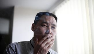 FILE - In this June 1, 2009 file photo, human rights lawyer Pu Zhiqiang, right, smokes a cigarette, at his office in Beijing. According to other Chinese activists on Tuesday, May 6, 2014, Chinese authorities have detained Pu in an apparent bid to deter activists from marking the upcoming 25th anniversary of a brutal military suppression of pro-democracy protesters. (AP Photo/Elizabeth Dalziel, File)