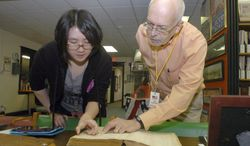 In this April 12, 2014 photo, Risako Doi, left, translates a Japanese Navy code book for Jim Kouzmanoff, president of the Vermilion County War Museum in Danville, Ill. Doi, a Japanese exchange student, has visited the museum a couple of times and has translated Japanese words on several items providing the museum staff with a better understanding of some of its items (AP Photo/Commercial-News, Matt Huber)