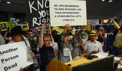 Protesters take over the City Council meeting, Monday May 5, 2014, in Albuquerque, N.M.  Alan Gomez was fatally shot by an APD officer in 2011. (AP Photo/The Albuquerque Journal, Bob Brawdy)