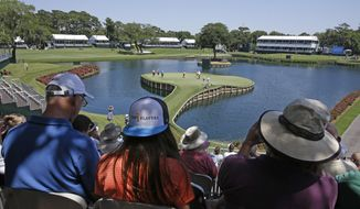 Spectators watch golfers on the 17th green during a practice round for The Players championship golf tournament at TPC Sawgrass in Ponte Vedra Beach, Fla., Tuesday, May 6, 2014. (AP Photo/John Raoux)