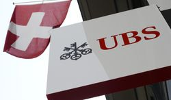 FILE - The April 24, 2014 file photo shows the logo of Swiss bank UBS and the Swiss flag in Zurich, Switzerland. Solid returns from its wealth management and investment banking divisions helped Switzerland's biggest bank, UBS AG, post a 7 percent profit advance in the first quarter.  (AP Photo/Keystone, Steffen Schmidt)