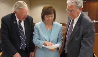 Sharron Angle, center, confers with Republican state Sen. Don Gustavson, left, and attorney Joel Hansen on Wednesday, May 7, 2014, in Carson City District Court following a hearing on challenges to Angle's initiative for a proposed constitutional amendment requiring photo identification to vote in Nevada. (AP Photo/Sandra Chereb)
