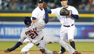 Houston Astros' Dexter Fowler (21) tries to distract Detroit Tigers second baseman Ian Kinsler as he throws to complete a double play on a Jason Castro ground ball in the sixth inning of a baseball game in Detroit, Wednesday, May 7, 2014. (AP Photo/Paul Sancya)