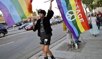 Bryan Kimpton, a supporter of the School Success and Opportunity Act (AB1266) waves a flag while celebrating at a rally organized by San Diego LGBTQ rights organizations Canvass for a Cause, SAME Alliance, and Black and Pink after a petition drive to place a proposition on the ballot to repeal the law failed to garner enough signatures Monday, Feb. 24, 2014, in San Diego. (AP Photo/Lenny Ignelzi)