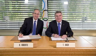 In this photo released by the International Olympic Committee (IOC), IOC President Thomas Bach, right, and Chairman and CEO of Comcast Corporation Brian L. Roberts pose for a photograph as they sign an agreement to secure the U.S. broadcast rights to the Olympics through to 2032 for NBC Universal, in Lausanne, Switzerland, Wednesday, May 7, 2014. NBC secured the U.S. broadcast rights to the Olympics through 2032 on Wednesday in a record six-games deal worth $7.75 billion. NBC already holds the rights through the 2020 Olympics in a four-games deal signed in 2011 for $4.38 billion. (AP Photo/Arnaud Meylan)