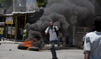 A student runs away from police dispersing a student protest in support of striking teachers as tires burn in Port-au-Prince, Haiti, Wednesday, May 7, 2014. Students are protesting to demand authorities respond to their striking teachers' demands for higher pay and improved working conditions. Students are concerned they will not be able to take exams which allow them to move on to the next level. Public school teachers across Haiti have been on strike for one week. (AP Photo/Dieu Nalio Chery)