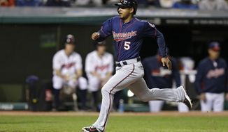 Minnesota Twins' Eduardo Escobar (5) races home to score on a sacrifice fly by Brian Dozier in the seventh inning of a baseball game against the Cleveland Indians Wednesday, May 7, 2014, in Cleveland. (AP Photo/Mark Duncan)
