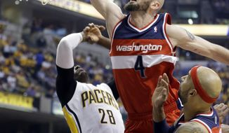 Washington Wizards center Marcin Gortat (4) get a dunks over teammate Drew Gooden, right, and Indiana Pacers center Ian Mahinmi during the first half of game 2 of the Eastern Conference semifinal NBA basketball playoff series Wednesday, May 7, 2014, in Indianapolis. (AP Photo/Darron Cummings)