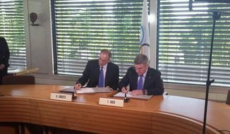 In this photo released by Patrick Sandusky of the United States Olympic Committee, International Olympic Committee (IOC) President Tomas Bach, right, and Chairman and CEO of Comcast Corporation Brian L. Roberts sign an agreement to secure the U.S. broadcast rights to the Olympics through to 2032 for NBC Universal, in Lausanne, Switzerland, Wednesday, May 7, 2014. NBC secured the U.S. broadcast rights to the Olympics through 2032 on Wednesday in a record six-games deal worth $7.75 billion. NBC already holds the rights through the 2020 Olympics in a four-games deal signed in 2011 for $4.38 billion. (AP Photo/Patrick Sandusky, USOC)