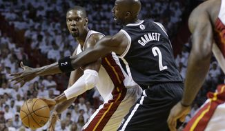 Miami Heat's Chris Bosh, left, passes as Brooklyn Nets' Kevin Garnett (2) defends in the first half of Game 1 in an Eastern Conference semifinal basketball game, Tuesday, May 6, 2014, in Miami. The Heat defeated the Nets 107-86. Bosh scored 15 points and grabbed 11 rebounds. (AP Photo/Lynne Sladky)