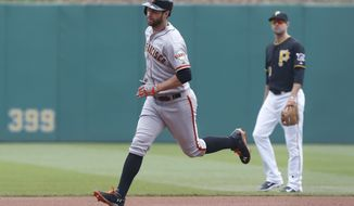 San Francisco Giants' Brandon Belt, left, rounds the bases past Pittsburgh Pirates second baseman Neil Walker after hitting a home run in the first inning of a baseball game on Wednesday, May 7, 2014, in Pittsburgh.  (AP Photo/Keith Srakocic)