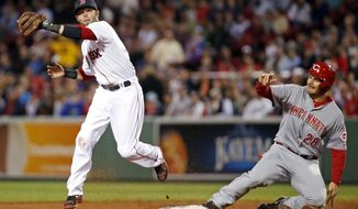 Cincinnati Reds' Chris Heisey (28) is forced at second base as Boston Red Sox second baseman Dustin Pedroia prepares to turn a double play on Reds' Zack Cozart during the fifth inning of a baseball game at Fenway Park in Boston, Wednesday, May 7, 2014. (AP Photo/Elise Amendola)