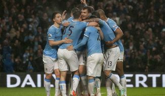 Manchester City's Edin Dzeko, centre, celebrates with teammates after scoring his second goal against Aston Villa during their English Premier League soccer match at the Etihad Stadium, Manchester, England, Wednesday May 7, 2014. (AP Photo/Jon Super)