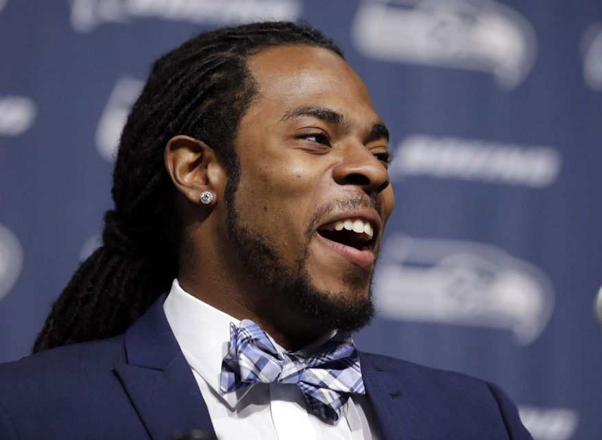 Seattle Seahawks' Richard Sherman smiles as he addresses a news conference Wednesday, May 7, 2014, at the team's headquarters in Renton, Wash. Sherman signed a four-year contract extension Wednesday with the Seahawks, a deal that makes him one of the highest-paid cornerbacks in NFL history. Sherman announced the deal on his website and later confirmed the new deal will keep him in a Seahawks uniform through the 2018 season. Sherman wrote that the extension is for $57.4 million with $40 million guaranteed. (AP Photo/Elaine Thompson)