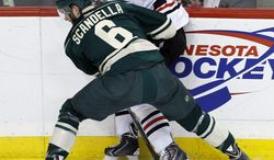 Minnesota Wild defenseman Marco Scandella (6) pins Chicago Blackhawks center Jonathan Toews (19) against the boards and away from the puck during the first period of Game 3 of an NHL hockey second-round playoff series in St. Paul, Minn., Tuesday, May 6, 2014. (AP Photo/Ann Heisenfelt)