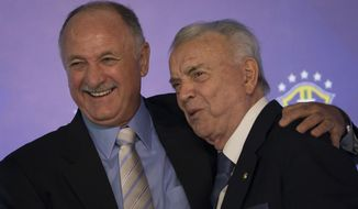 Brazil's soccer coach Luiz Felipe Scolari. left, embraces Brazilian Soccer Confederation President Jose Maria Marin during a news conference to anouce his list of players for the 2014 Soccer World Cup in Rio de Janeiro, Brazil, Wednesday, May 7, 2014. The team will mix talented young stars such as Neymar and Oscar with more experienced players such as Dani Alves, David Luiz, Thiago Silva and Hulk. (AP Photo/Felipe Dana)