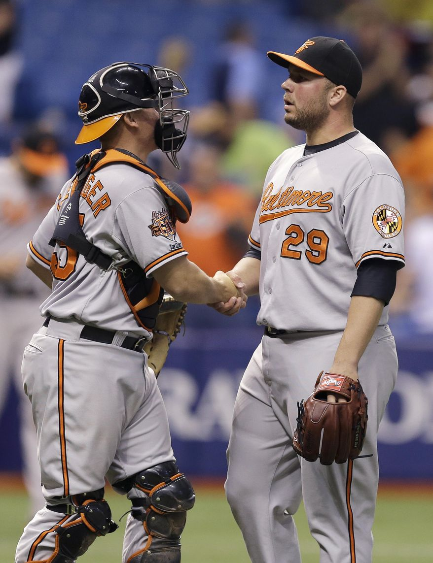 Baltimore Orioles relief pitcher Tommy Hunter, right, shakes hands with catcher Steve Clevenger after closing out the Tampa Bay Rays during the ninth inning of a baseball game Tuesday, May 6, 2014, in St. Petersburg, Fla. The Orioles won 5-3. (AP Photo/Chris O'Meara)