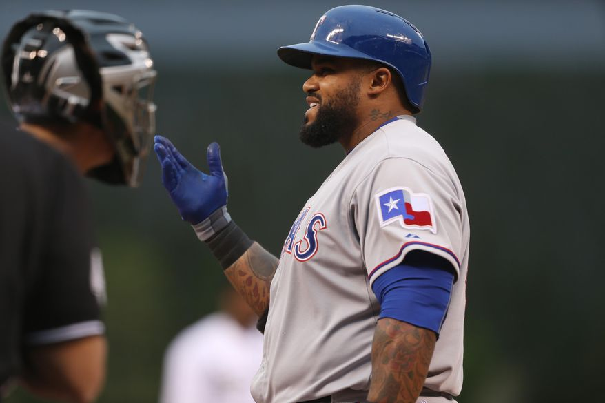Texas Rangers' Prince Fielder, right, argues a called strike three with home plate umpire Kerwin Danley to end the top of the first inning against the Colorado Rockies Texas of in an interleague baseball game in Denver on Tuesday, May 6, 2014. (AP Photo/David Zalubowski)