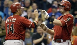 Arizona Diamondbacks' Paul Goldschmidt is congratulated by Martin Prado (14) after Goldschmidt hit a two-run home run during the third inning of a baseball game against the Milwaukee Brewers Wednesday, May 7, 2014, in Milwaukee. (AP Photo/Morry Gash)