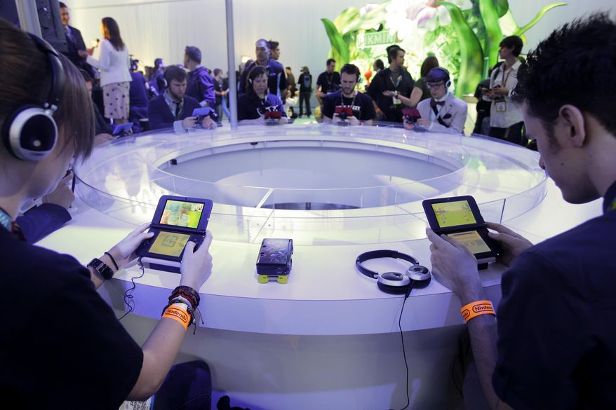 "FILE- In this June 11, 2013 file photo, attendees play video games on the Nintendo 3DS at the Nintendo Wii U software showcase during the E3 game show in Los Angeles. The gaming company said Tuesday, May 6, 2014, it wouldn't bow to pressure to allow players to engage in romantic entanglements with characters of the same sex in the English version of ""Tomodachi Life"" following a social media campaign launched last month seeking virtual equality for the game's characters, which are modeled after real people. (AP Photo/Jae C. Hong, file)"