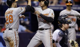 Baltimore Orioles' Jonathan Schoop, center, celebrates with Steve Pearce, left, after hitting a two-run home run off Tampa Bay Rays relief pitcher Brandon Gomes during the seventh inning of a baseball game Wednesday, May 7, 2014, in St. Petersburg, Fla. Catching for the Rays is Ryan Hanigan. (AP Photo/Chris O'Meara)