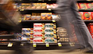 FILE - In this Feb. 9, 2011 file photo, a shopper passes a shelf full of Nabisco products - Premium saltines, Triscuits, Ritz crackers and Wheat Thins - at a Ralphs Fresh Fare supermarket in Los Angeles. Nabisco is a Mondelez International brand. Mondelez International reports quarterly earnings on Wednesday, May 7, 2014. (AP Photo/Reed Saxon, File)