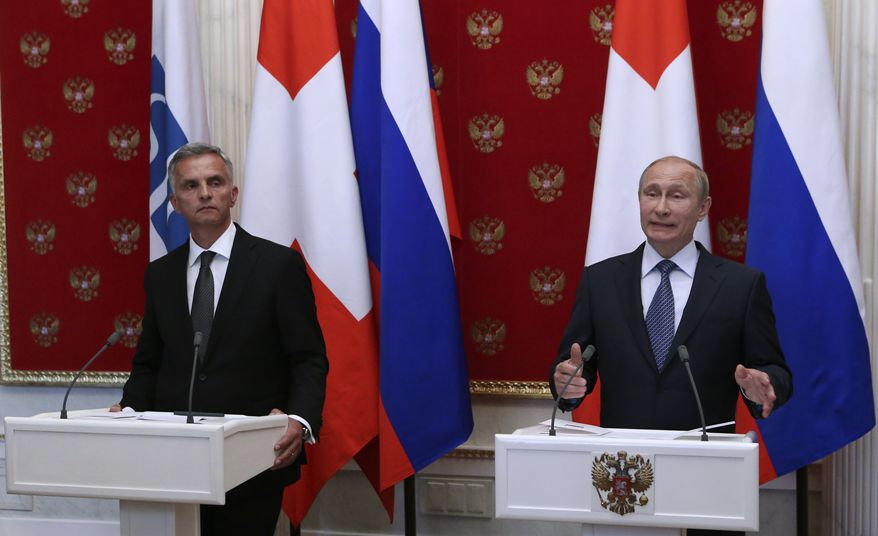 Russian President Vladimir Putin, right, and Swiss Federal President Didier Burkhalter hold a joint news conference in the Kremlin in Moscow, Wednesday, May 7, 2014. Russia has pulled back its troops from the Ukrainian border, Vladimir Putin told diplomats Wednesday as he urged insurgents in southeast Ukraine to postpone their planned referendum Sunday on autonomy. (AP Photo/Sergei Karpukhin, Pool)