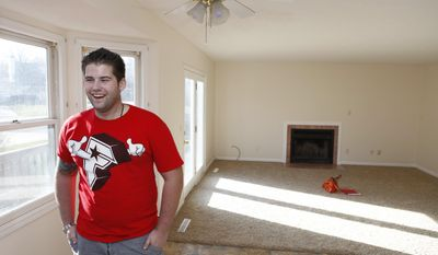 Jacob Hutchinson, who had both legs and an arm injured while serving in the Iowa National Guard in Afghanistan, stands in the living room of his new home Nov. 28, 2012 in Bloomington, Ind.  Hutchinson wore the physical wounds of war. Jagged scars from an improvised explosive device that nearly tore off his lower legs. Precision-cut lines from more than 20 surgeries to repair the damage.  But it was the emotional toll from serving as a combat medic in Afghanistan that likely caused the 24-year-old National Guard veteran and Purple Heart recipient to kill himself on April 22 inside the Bloomington house a military organization had donated to him.  (AP Photo/Bloomington Herald-Times, Jeremy Hogan)