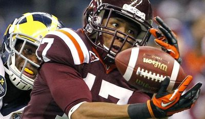 Virginia Tech cornerback Kyle Fuller (17) intercepts a pass intended for Michigan wide receiver Junior Hemingway (21) during the first quarter of the Sugar Bowl NCAA college football game in New Orleans, Tuesday, Jan. 3, 2012. (AP Photo/Dave Martin)