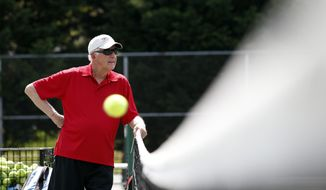 Marty Dowd, tennis coach for Catholic University of America, watches practice, Thursday, May 8, 2014 in Washington. The 77-year-old coach led the Cardinals to the Landmark Conference title and a first-round match against Washington & Lee in the NCAA Division III bracket. (AP Photo/Alex Brandon)